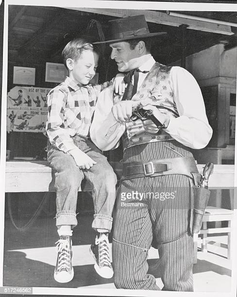 Dressed in the outfit he wears as TV's Wyatt Earp on the ABCTV series Actor Hugh O'Brien gives a gun safety lesson to sevenyear old Douglas Meservey...