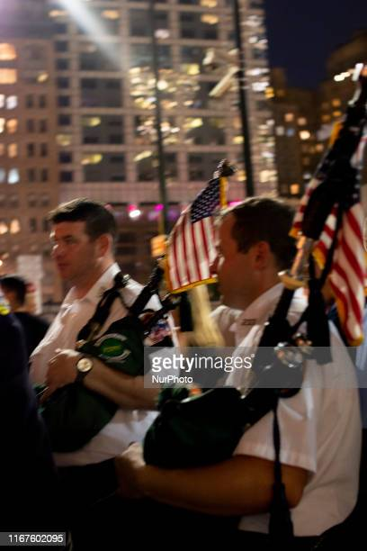Dressed in their ceremonial Irish kilts with bagpipes two members of the New York Fire Department walk through the crowds during the Tribute in...