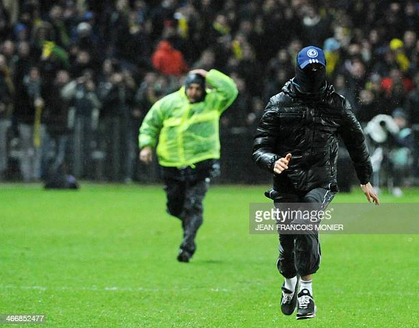 A dressed streaker runs on the field during the French League Cup football match between Nantes and Paris SaintGermain at the La Beaujoire stadium in...