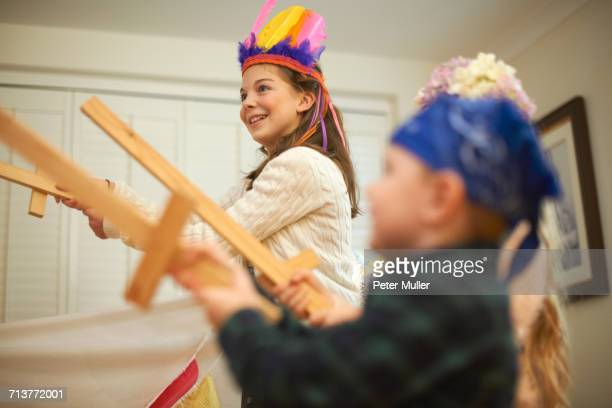 dressed up boy and two sisters having sword fight - rough housing stock photos and pictures