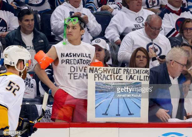 A dressed up fan holds up a sign heckling the Nashville Predators during the pregame warm up prior to NHL action against the Winnipeg Jets in Game...