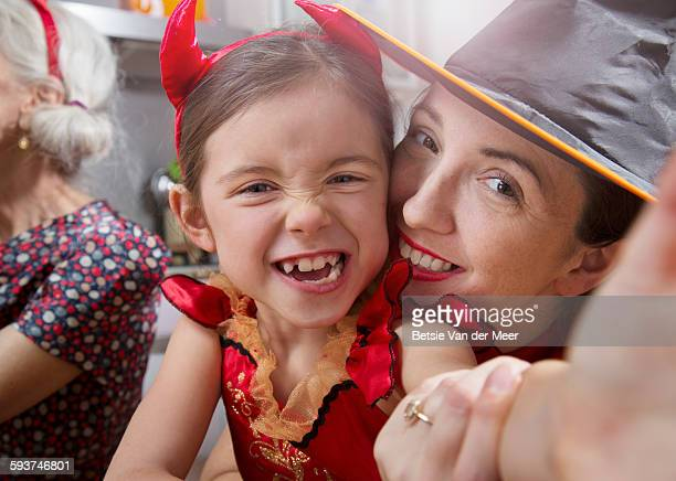 dressed up girl takes selfie of herself and mother - devil costume stock photos and pictures