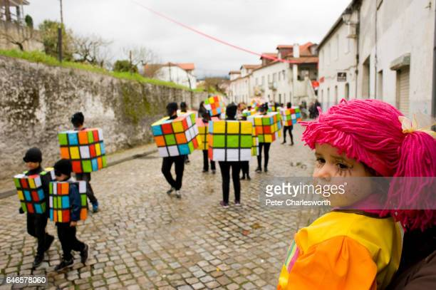 A dressed up girl watches people dressed as Rubik's cubes parade in the carnival procession through the main street of the mountain town of Coja