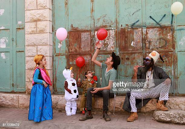 TOPSHOT Dressed up Israeli settlers take part in a parade during the festivities of the Jewish holiday of Purim on March 24 2016 in the West Bank...