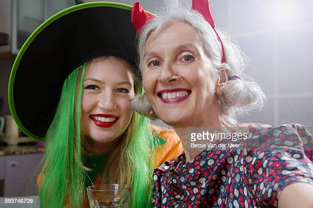 Dressed up mother and daughter take Selfies.