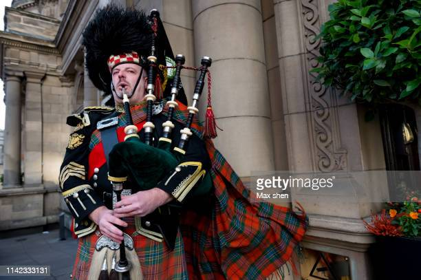 a dressed up scottish man playing bagpipe in the street - traditional musician stock photos and pictures