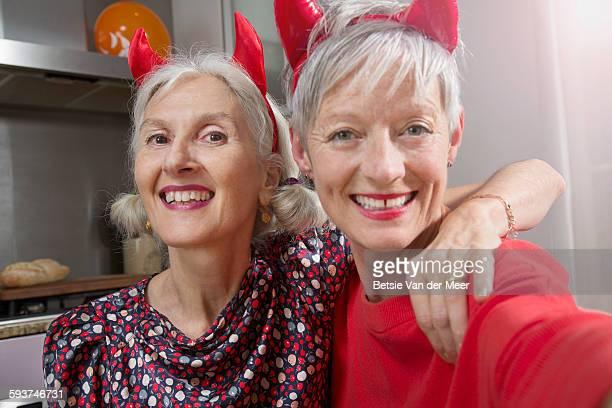 Dressed up senior women take Selfies.