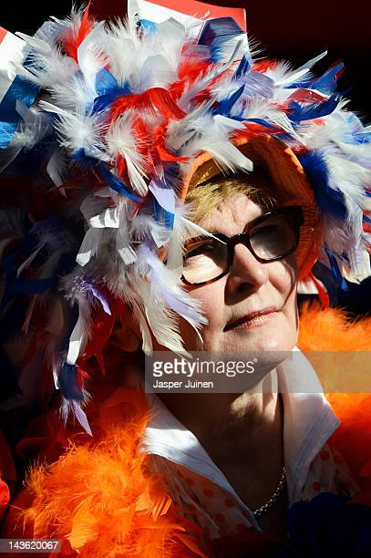 A dressed up spectator enjoys the sun as she waits for Dutch Queen Beatrix of the Netherlands to arrive during the traditional Queens Day...
