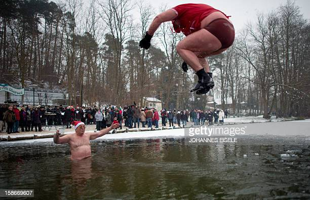 A dressed up winter swimmer jumps into the cold water during a traditional ice swimming session on December 23 2012 in Lanke some 50 kilometers north...