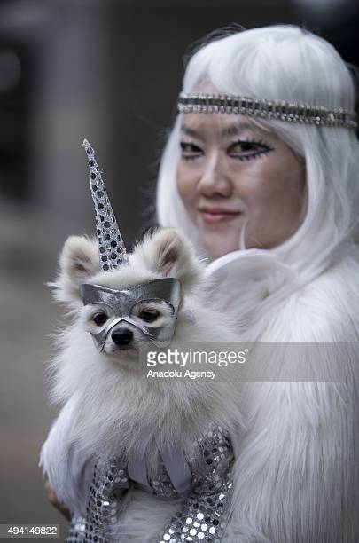 A dressed up woman holds her dog during Halloween Dog Parade at Tompkins Square in Manhattan New York on October 25 2015