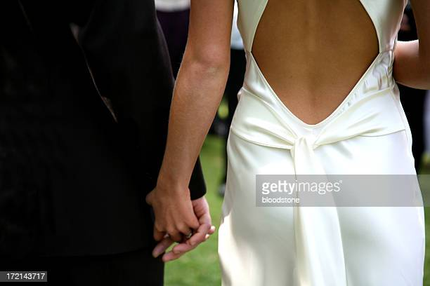 Dressed-up couple holding hands walking to the aisle