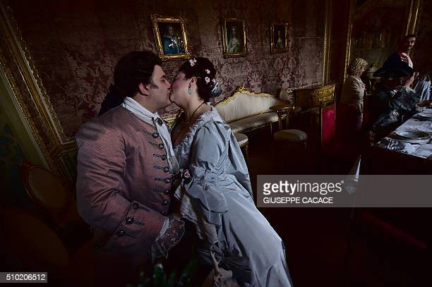 Dressedup in eighteenth century costumes a man and woman kiss to celebrate Valentine's Day in one of the rooms of the royal hunting lodge and...