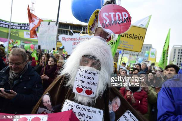 A dressedup protester has a placard over his mouth reading 'The fight is far from over' on January 20 2018 in Berlin during a demonstration under the...