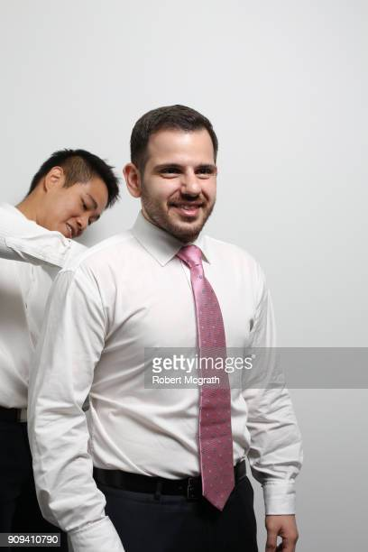 Dresser adjusts young male professional's business shirt