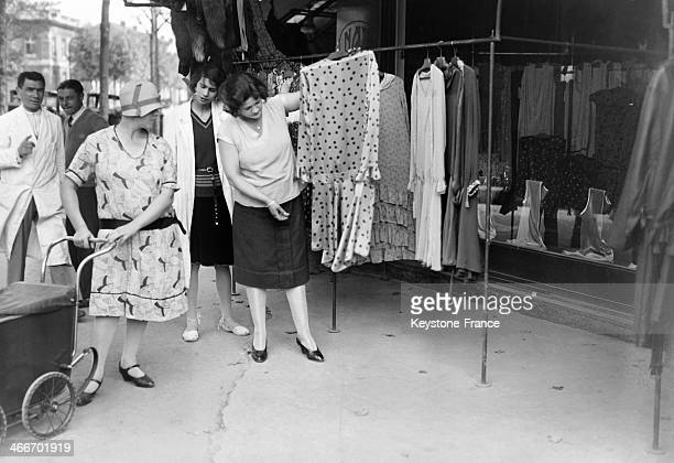 Dresses hanging on clothes rack outside a cloting store in September 1929 in Paris France