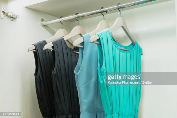 dresses hanging on rack in store - blue dress stock pictures, royalty-free photos & images