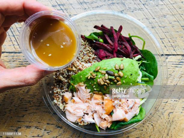 dressing a salmon, avocado and quinoa salad - salad dressing stock pictures, royalty-free photos & images