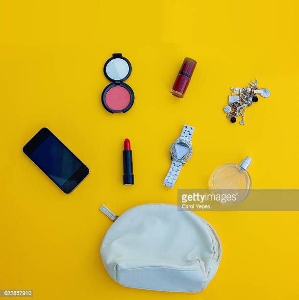 Dressing case with a lot of feminine objects.yellow background
