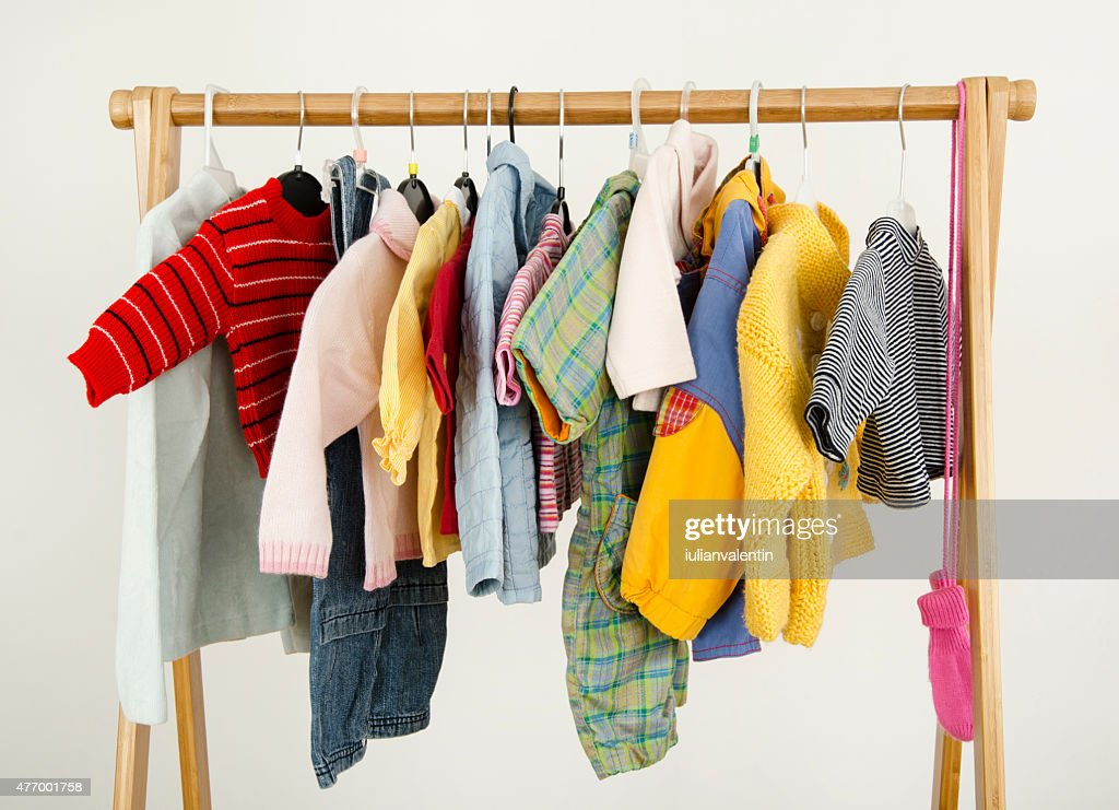 Dressing closet with baby clothes arranged on hangers. : Stock Photo