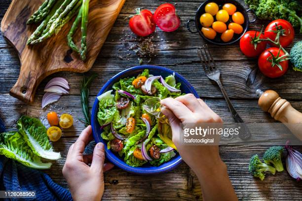 dressing fresh organic vegetables salad with olive oil - salad dressing stock pictures, royalty-free photos & images