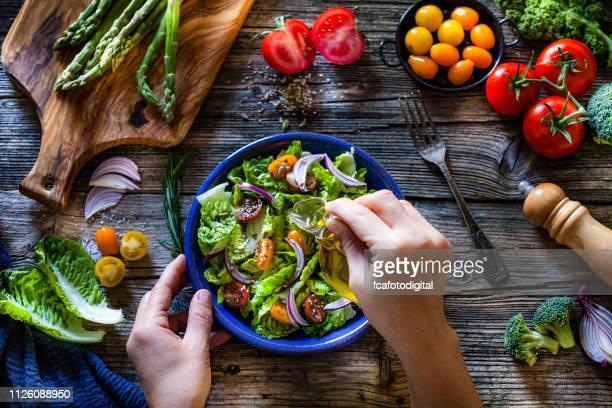 frisches bio-gemüse-salat mit olivenöl dressing - gesunde ernährung stock-fotos und bilder