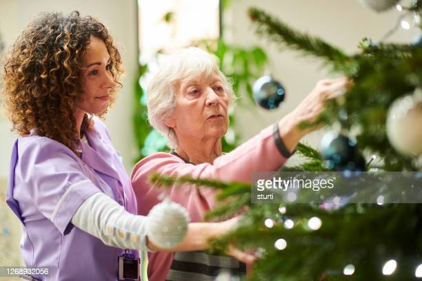 dressing the tree in the care home - christmas stock pictures, royalty-free photos & images