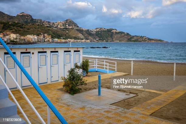 dressingroom on the beach of giardini naxos, taormina and castelmola in the background - finn bjurvoll stock pictures, royalty-free photos & images