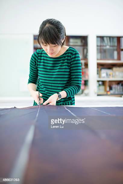 Dressmaker cutting a dark blue fabric.