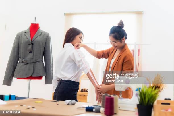 dressmaker, fashion designer and tailor concept - young dressmaker women over clothes rack with dresses background - デザイナー服 ストックフォトと画像