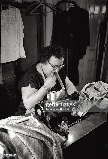 A dressmaker is sewing pieces of clothing on a Singer sewing machine with a picushion nearby in her hands she holds a pair of scissors New York