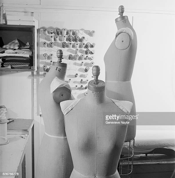 Dressmaker's dummies stand near a board filled with spools of thread in a designer's shop in Manhattan