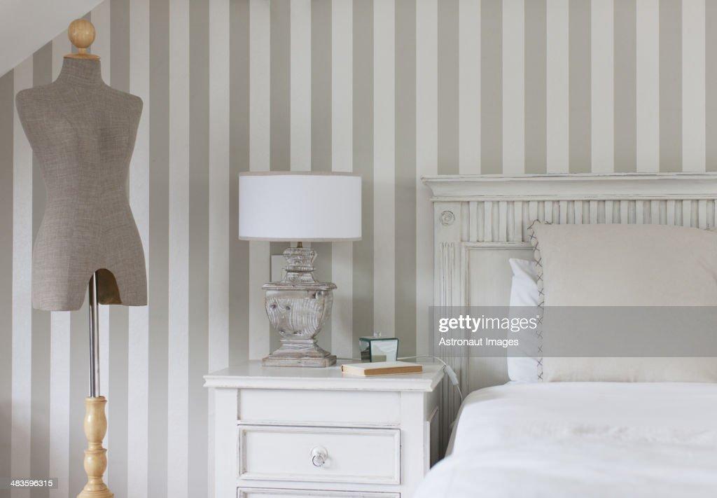 Dressmakers model and bed in feminine bedroom : Stock Photo