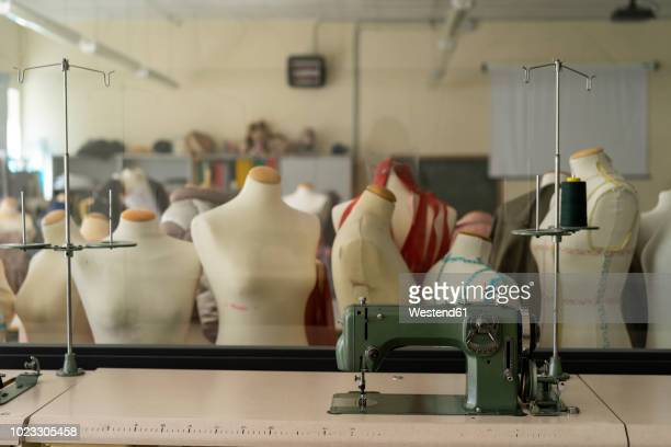 dressmaker's models and sewing machine in fashion designer's studio - dressmaker's model stock photos and pictures