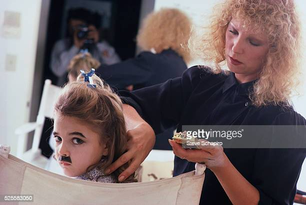 Drew Barrymore being made up for a photo shoot as Charlie Chaplin's Tramp