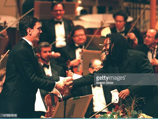 Drew Bledsoe gets a standing ovation at Symphony Hall and receives congratulations from Bobby McFerrin who was the night's guest conductor and...