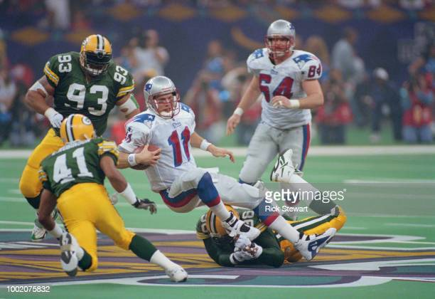 Drew Bledsoe Quarterback of the New England Patriots is sacked by Sean Jones of the Green Bay Packers with help from teammates Eugene Robinson and...