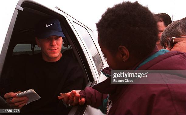 Drew Bledsoe shakes hands with 6yearold Kammy before signing autographs for fans outside Foxboro Kammy's mother Paula Taylor holds her up to the car...