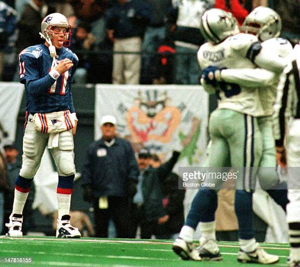 Drew Bledsoe walks off the field dejected as Darren Woodson is congratulated by a teammate after his second interception of the game