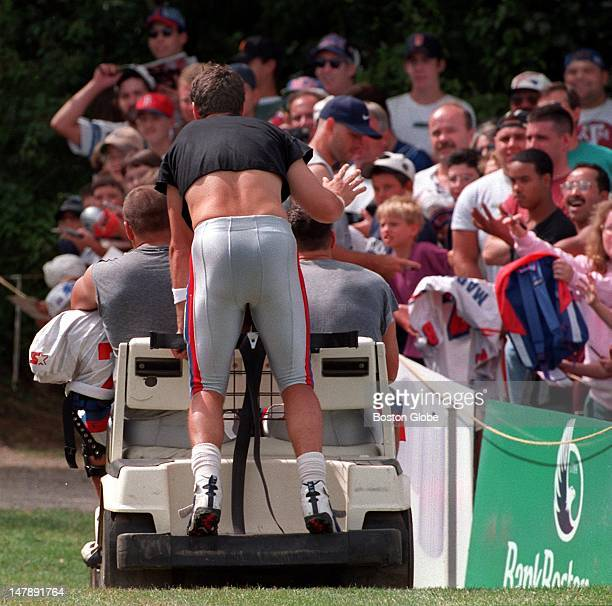 Drew Bledsoe waves to fans from the back of a golf cart on his way back to the locker room after the workout