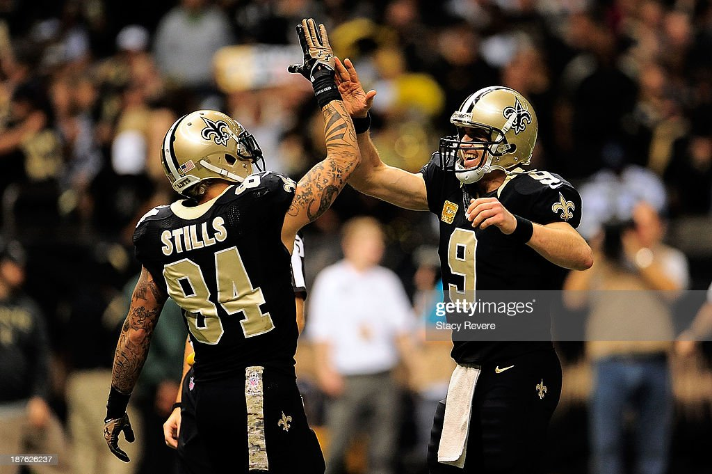Drew Brees #9 and Kenny Stills #84 of the New Orleans Saints celebrate a touchdown against the Dallas Cowboys during a game at the Mercedes-Benz Superdome on November 10, 2013 in New Orleans, Louisiana.