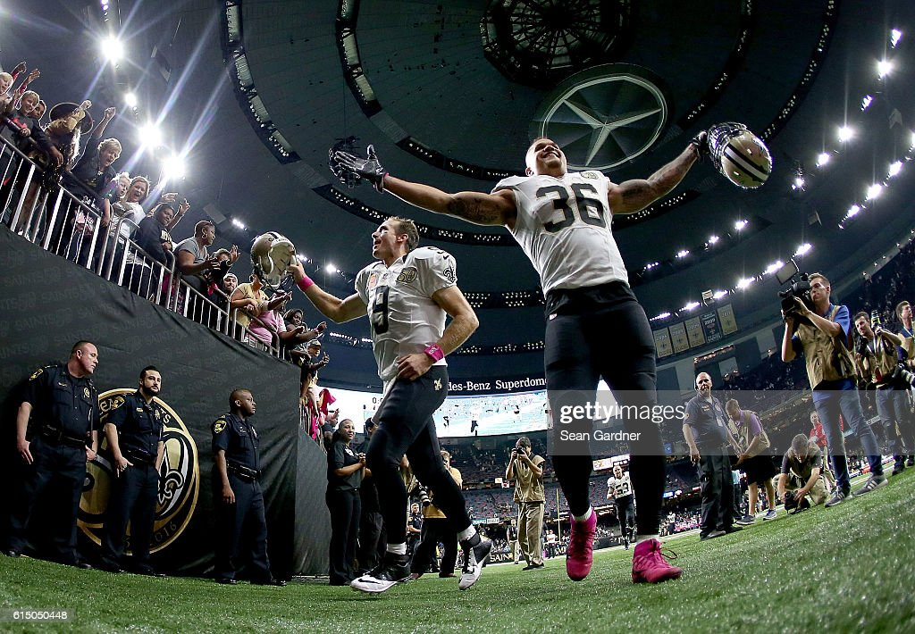Drew Brees #9 of the New Orleans Saints and Daniel Lasco #36 celebrate after defeating the Carolina Panthers 41-38 at the Mercedes-Benz Superdome on October 16, 2016 in New Orleans, Louisiana.