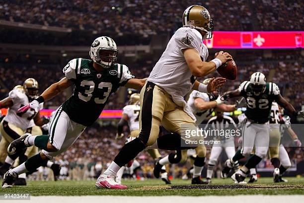 Drew Brees of the New Orleans Saints avoids a tackle by Eric Smith of the New York Jets at the Louisana Superdome on October 4 2009 in New Orleans...