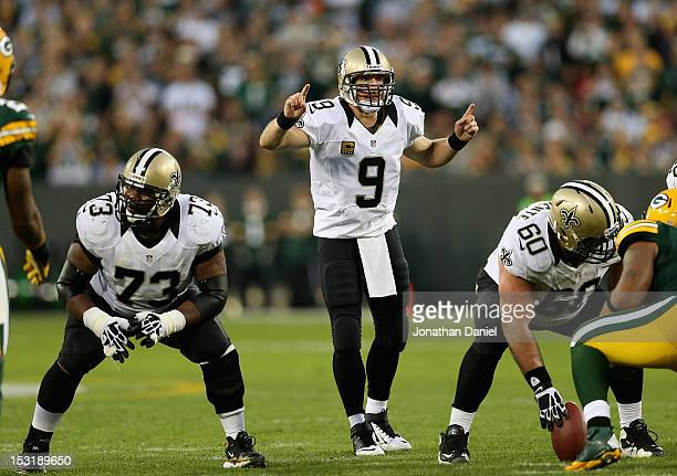 Drew Brees of the New Orleans Saints calls a play as Jahri Evans and Brian de la Puente await the snap against the Green Bay Packers at Lambeau Field...