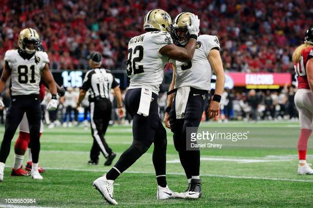 Drew Brees of the New Orleans Saints celebrates a rushing touchdown with Benjamin Watson during the fourth quarter against the Atlanta Falcons at...
