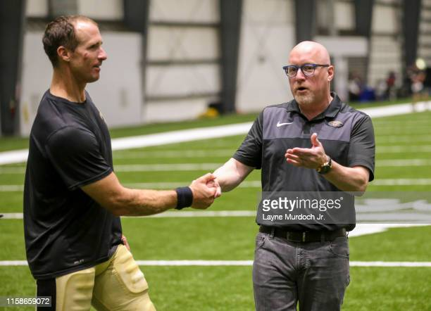 Drew Brees of the New Orleans Saints daps up Vice President David Griffin of the New Orleans Pelicans during the New Orleans Saints Quarterback...