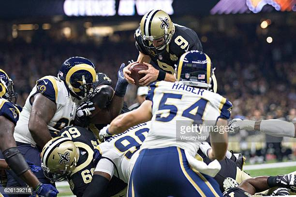 Drew Brees of the New Orleans Saints dives over the pile for a touchdown in the first half of a game against the Los Angeles Rams at MercedesBenz...