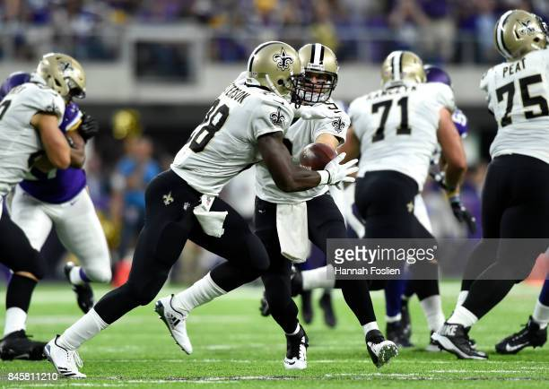 Drew Brees of the New Orleans Saints hands the ball off to Adrian Peterson in the first half of the game on September 11 2017 at US Bank Stadium in...