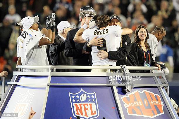 Drew Brees of the New Orleans Saints holds up the Vince Lombardi Trophy and hugs head coach Sean Payton after defeating the Indianapolis Colts during...