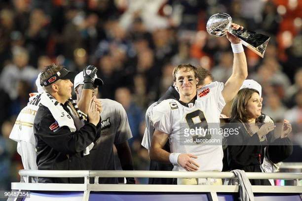 Drew Brees of the New Orleans Saints holds up the Vince Lombardi Trophy as head coach Sean Payton looks on after defeating the Indianapolis Colts...