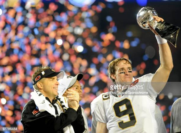 Drew Brees of the New Orleans Saints holds up the Vince Lombardi Trophy on the podium as head coach Sean Payton looks on after defeating the...